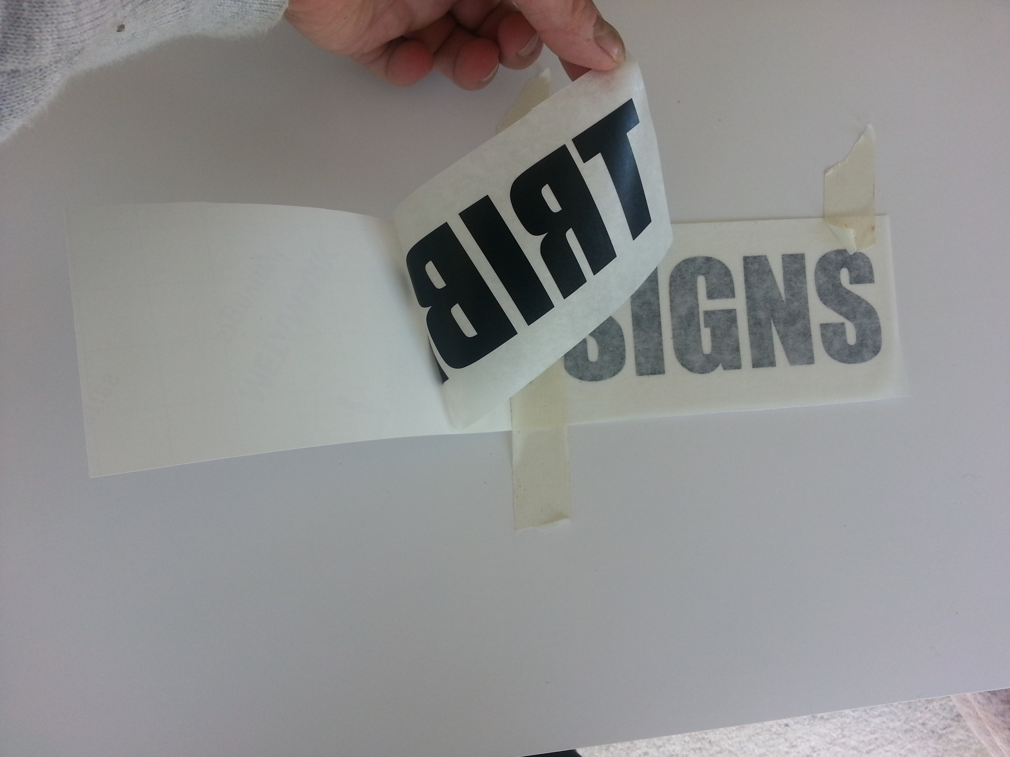 vinyl lettering example showing backing paper, application tape and the vinyl